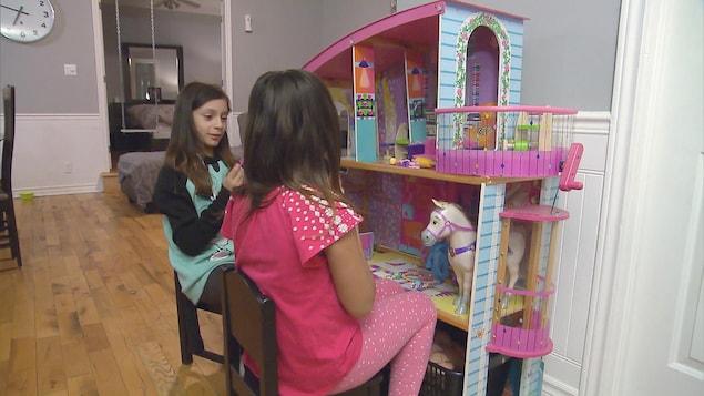 Thalya et sa soeur jouent avec leur maison de poupées