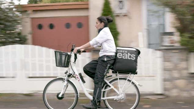 une femme sur un vélo, un sac de livraison UBER EATS à l'arrière, un pantalon DELIVEROO