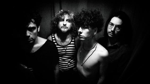 Les 4 hommes sont photographiés en noir et blanc.