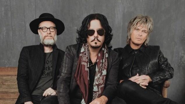 Les trois musiciens du groupe, vêtus de noir, posent pour une photo promotionnelle.