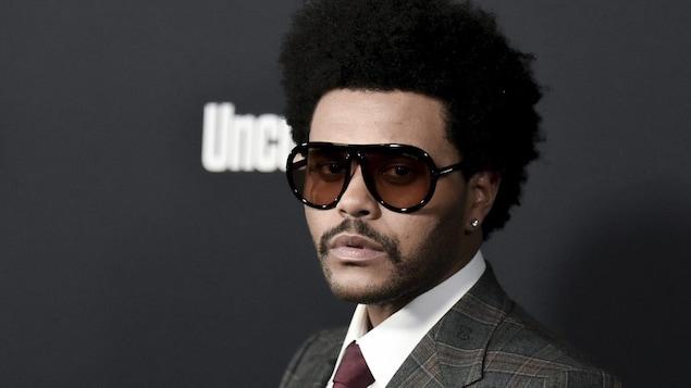 L'homme vêtu d'un veston et portant des lunettes fumées prend la pose pour les caméras sur un tapis rouge.