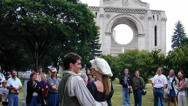 Un homme et une femme en costume d'époque jouent une scène à l'extérieur devant des spectateurs.