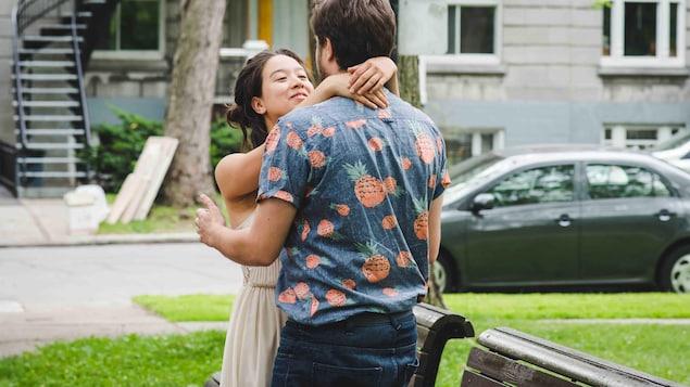 À l'extérieur, une femme est debout devant un homme de dos qu'elle tient par le cou. Elle sourit.