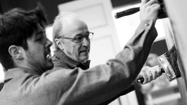 Les comédiens Steeven Lee Potvin et Michel Nadeau sont en train de peindre.