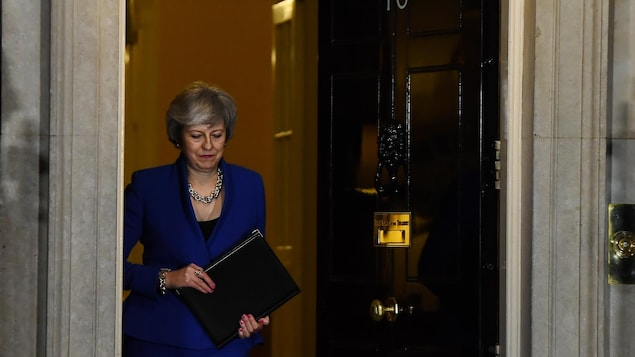 Theresa May, regardant au sol et tenant un porte-document, sort par l'entrée principale du 10 Downing Street, à Londres.