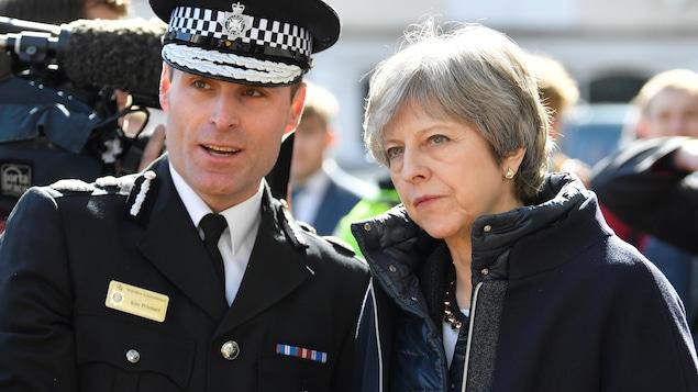 À gauche, un policier britannique vêtu d'une casquette, et à droite, Theresa May.