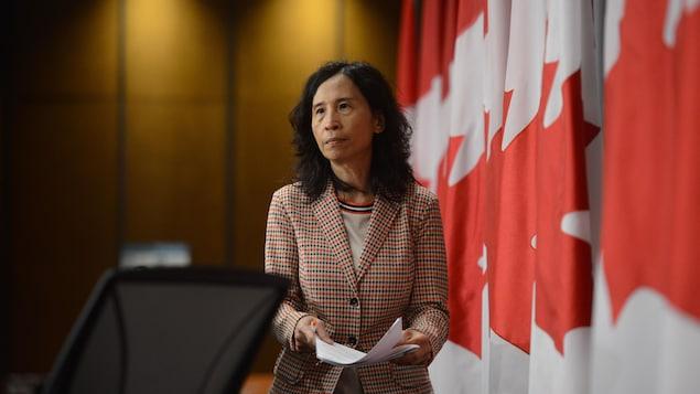 Theresa Tam à Ottawa avec des drapeaux canadiens derrière elle.