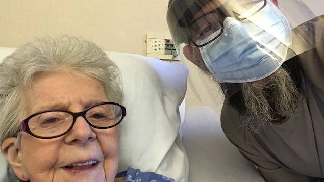 Thérèse Marineau, assise dans son lit, pose en compagnie de son fils Réal Migneault, qui porte un masque et une visière.