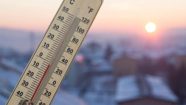 Un thermomètre se trouve devant un paysage ensoleillé.