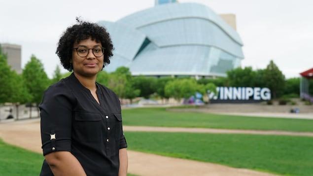 Une femme avec le Musée canadien pour les droits de la personne derrière elle.