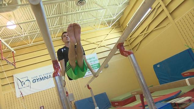 Thierry Pellerin s'exerce dans un club de gym. Il soulève sont poids, les deux jambes vers l'avant, les bras tendus sur des barres latérales.