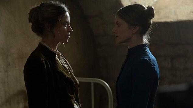 2 femmes portant des vêtements du 19e siècle se tiennent debout l'une en face de l'autre.