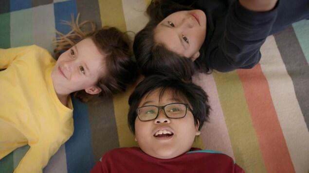 Trois enfants souriants couchés sur le dos.