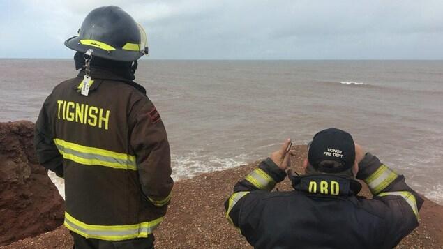 Deux pompiers scrutent la mer, l'un d'eux emploie des jumelles