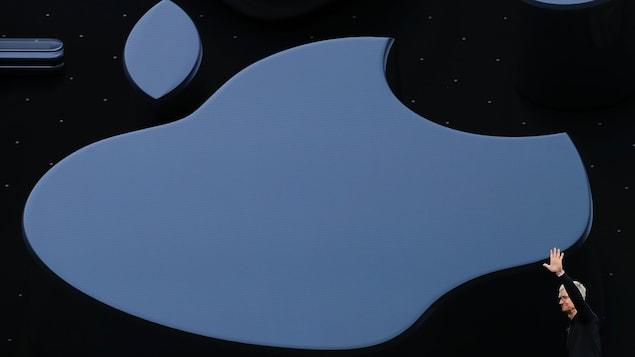 Tim Cook envoie la main sur une scène devant un immense logo d'Apple projeté sur un écran.