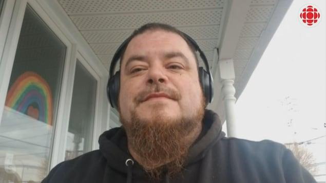 Un homme à la longue barbe porte des écouteurs sur la tête. Derrière lui, un arc-en-ciel est peint dans la fenêtre de sa maison.