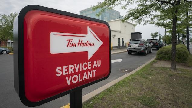 Des voitures attendent en file au service au volant d'un restaurant Tim Hortons.