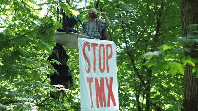 Le Dr Tim Takaro sur une plateforme dans un arbre avec une bannière où l'on peut lire Stop TMX.