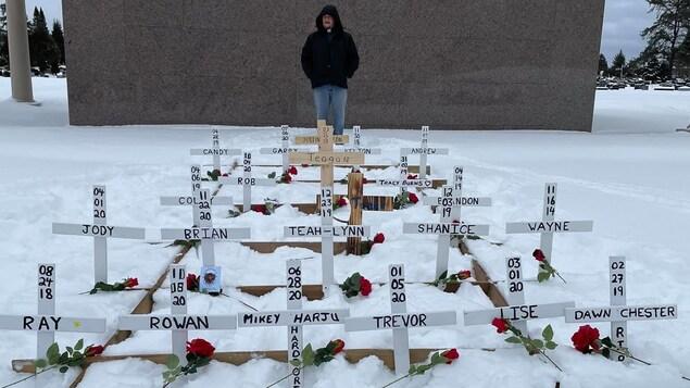 Des croix blanches sont plantées dans la neige avec des roses et le nom des défunts.