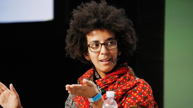 Une femme assise, équipée d'un micro, s'exprime sur scène.