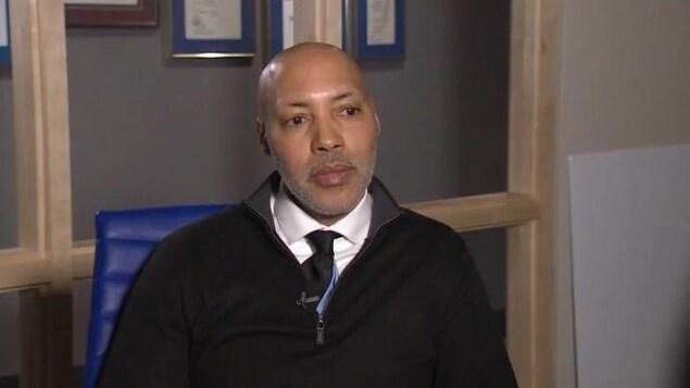 Un homme noir portant une chemise avec une cravatte.
