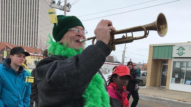 Rosaire Roy porte une écharpe de plumes vertes et souffle à la trompette.