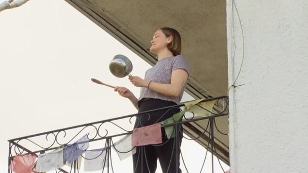 Une femme participant au tintamarre depuis son balcon.