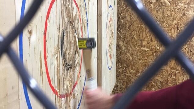Une clôture sépare deux cibles de lancer à la hache.