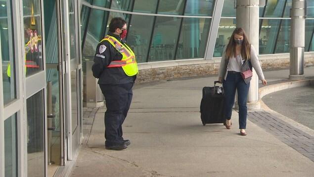 Une femme portant un masque tire sa valise devant l'entrée d'un aéroport. Un garde de sécurité portant aussi un masque la regarder entrer.