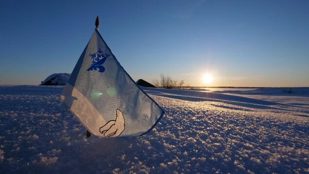 Un petit drapeau bleu et blanc arborant les symboles d'un ours polaire et d'un logo représentant une moitié de fleur de lys et une moitié de flocon est planté dans la neige.