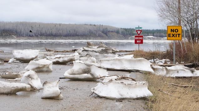 Des blocs de glacebloquent une rue devant le fleuve.