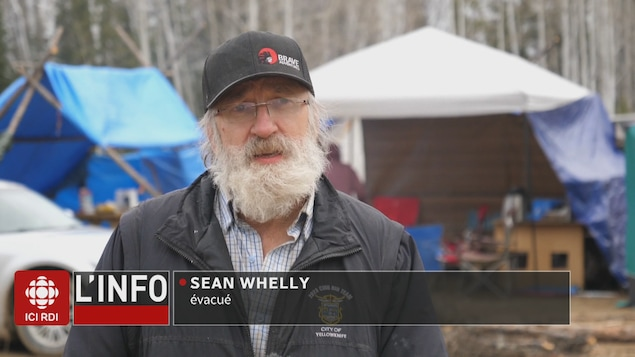 Sean Whelly devant une tente.