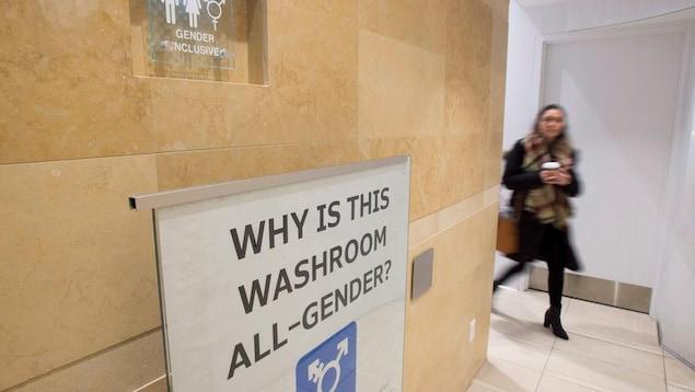 Une affiche devant une salle de toilettes.