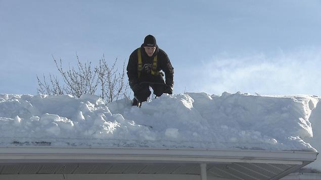 Un entrepreneur déneige un toit.