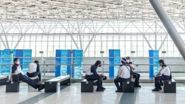 Security guards sit in the IBC/MPC Tokyo International Exhibition Centre ahead of the 2020 Olympic Games on July 20 in Tokyo. Set to begin on Friday, the event was touted as safe and secure by organizers, but has so far been plagued by COVID-19 infections.