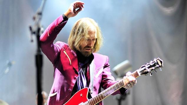 Le musicien Tom Petty jouant de la guitare sur scène.