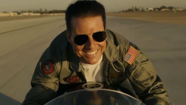Tom Cruise est sur sa moto et il sourit.