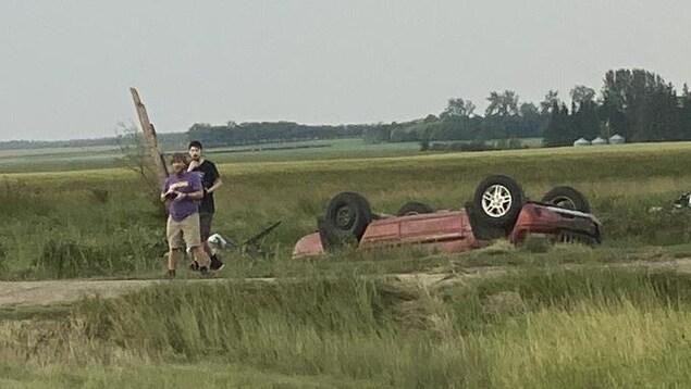 Deux personnes près d'une voiture renversée dans un champ.