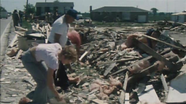 Une femme et un homme fouillent dans les décombres à Masson-Angers. (Archives)