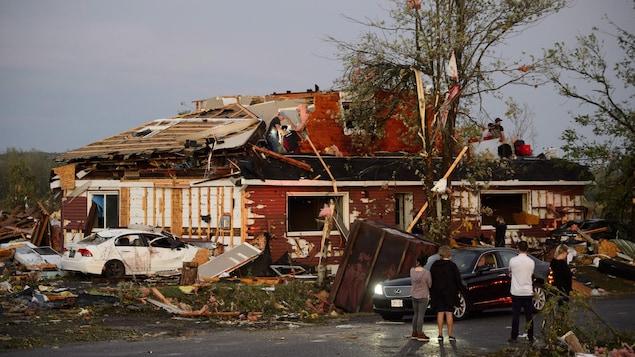 Plusieurs personnes sont debout dans la rue ou sur le toit d'une maison en ruines.