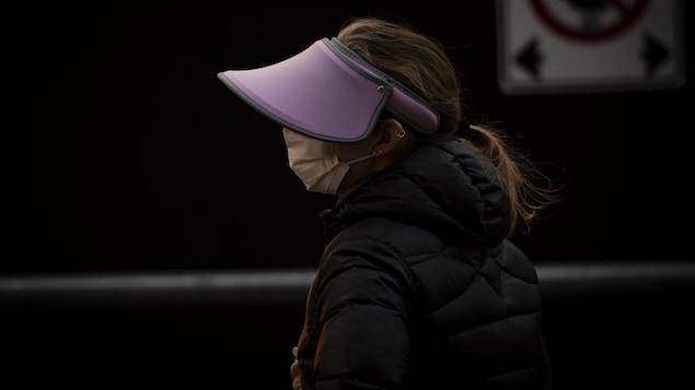 Une personne portant un masque et un chapeau à large visière marche dans la rue.