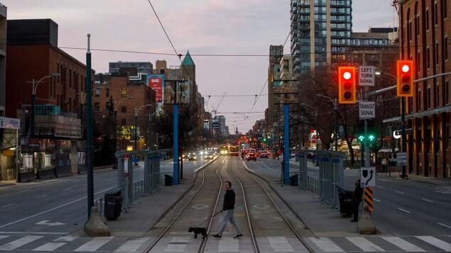 Un homme traverse une rue largement désertée de Toronto.