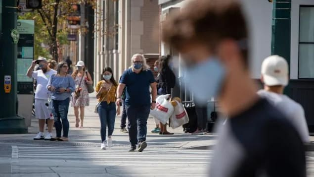 Des gens marchent dans la rue avec un masque.