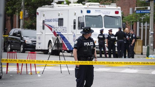 Des policiers s'affairent à l'intérieur du périmètre de sécurité de la fusillade.