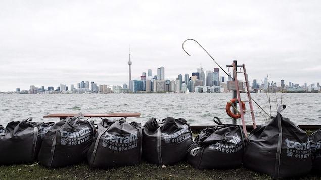 Des sacs de sable sur une des îles de Toronto et le centre-ville au loin
