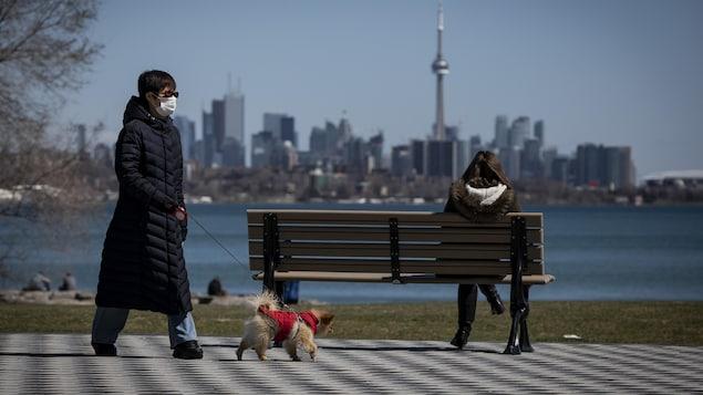 Une femme avec un masque passe à distance d'un banc public où est assis une autre femme qui regarde la ville de Toronto.