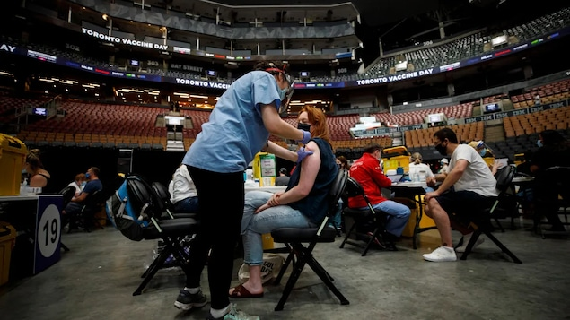 A Toronto resident receives a COVID-19 vaccine at a mass vaccination clinic held inside Scotiabank Arena in late June. Experts have stressed the need for Canadians to keep getting vaccinated to protect themselves as best as possible from variants of the novel coronavirus that cases COVID-19, such as lambda. (Cole Burston/The Canadian Press)