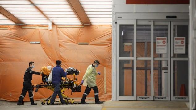 加拿大多伦多市,医护人员在把一名新冠患者推入医院,多伦多是加拿大受新冠疫情影响最严重的城市之一。