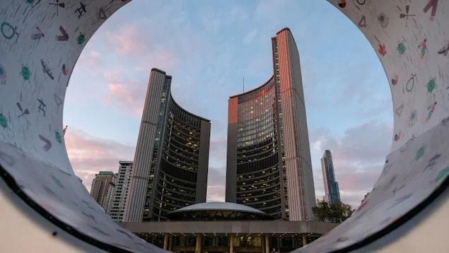 L'hôtel de ville de Toronto, vu du sol à travers une structure en forme de cercle.