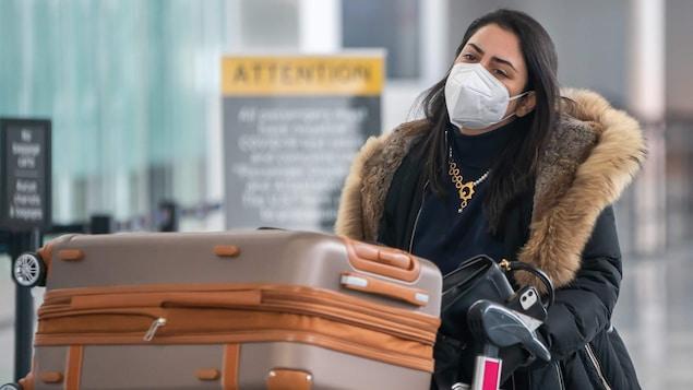 Une voyageuse portant un masque pousse un chariot rempli de valises à l'aéroport Pearson.
